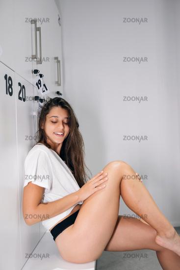 Sexy brunette girl in black underwear sitting on the bath