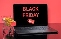 Modern laptop computer with Black Friday sale screen with shopping cart and gold coins