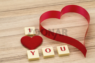 valentine's paper hearts on a wooden background and tex i love you