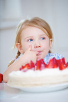 Mädchen kostet heimlich von Erdbeertorte
