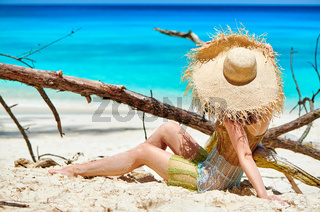 Woman sitting on beach at Seychelles