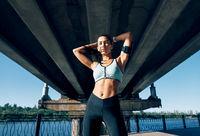 Beautiful confident woman in sportswear posing outdoors
