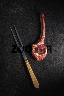 Slices raw lamb chops and fork