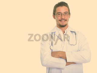 Studio shot of young happy man doctor smiling with arms crossed isolated against white background