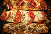 Long baguettes pizza sandwiches with tuna, mushrooms, tomatoes and cheese on a metal baking tray