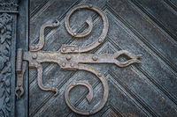 Closeup on vintage iron hinges in baroque style on wooden door