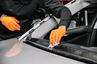 Close up, Car glazing, fixing and repairing a windshield. Windscreen replace process of a car at a garage service. Cleaning a dashboard.