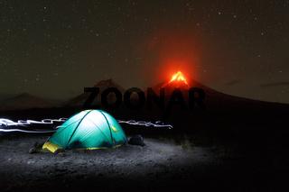Illuminated touristic camping at night on background eruption active volcano of Kamchatka Peninsula