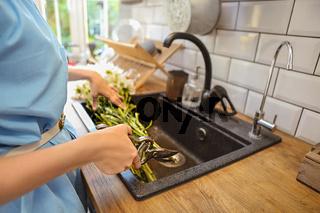 Crop woman cutting flowers in sink