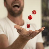 Man juggles with red dices