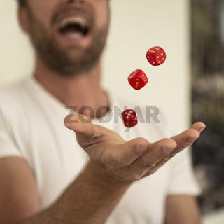 Mann jongliert mit roten Würfeln
