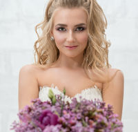 Young bride in studio with exquisite bouquet