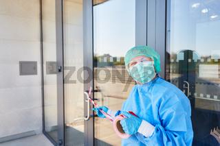 Mitarbeiter bringt Absperrung an Tür von Klinik an wegen Coronavirus