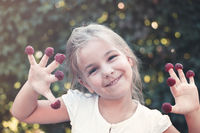 Smiling little child with raspberry outdoors