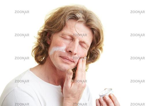 Mann pflegt sein Gesicht