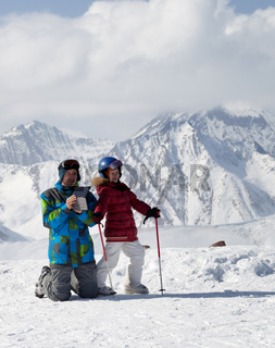Little skier and her father on top of snowy ski slope