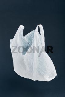 White empty plastic bag floating over black background