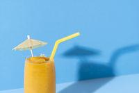 Glass of mango smoothie. Yellow slush with a cocktail umbrella