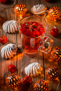 Spicy winter tea or punch with anise and meringue pastry with Christmas lights
