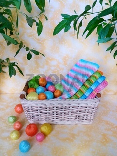 A beige wicker basket with balls of colored yarn and knitted hats.