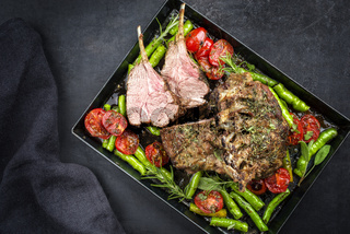 Barbecue rack of lamb neck with paprika and tomato offered as top view on a metal tray with copy space