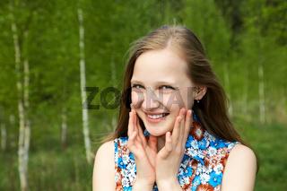 The smiling girl among trees
