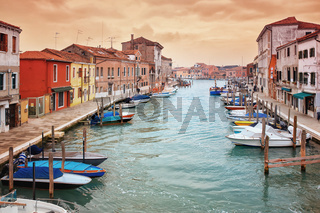 Narrow canal among old colorful houses on island of Murano