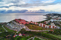 Almuñécar seaside hillside town aerial photo, above drone point of view. Picturesque hills, valleys, agricultural land scape. Moody cloudy sky over Mediterranean Sea. Granada province, Costa Tropical