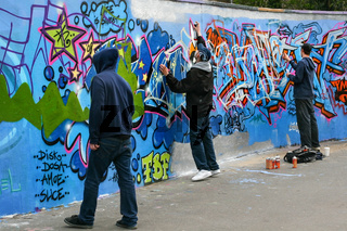 London, United Kingdom - April 20th, 2008: Three boys painting graffiti with sprays on concrete wall during day