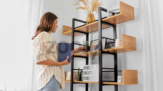 woman arranging flower and books at home