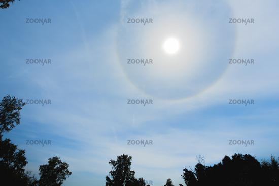 Atmospheric optical effect circle around the sun on hot summer day. Atmospheric halo phenomenon arou