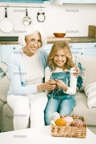Granddaughter visits her grandmother for knitting