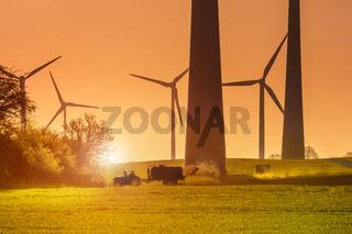 Landwirtschaft, Düngung im Morgengrauen, vor Windrädern, Bio Landwirt, natürliche energie