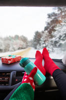 The girl is holding a thermos while sitting in the car in winter, on the background of the winter forest. Travel, trip and winter concept.