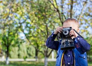 Little boy taking pictures in a park