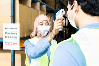 Muslim asian warehouse worker take temperature to another worker