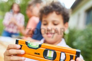 Junge hält Wasserwaage im Workshop im Ferienlager