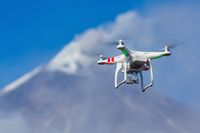 Flying drone quadcopter UAV aerial photography in sky on background volcano eruption
