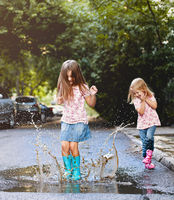 Happy sisters playing in puddle