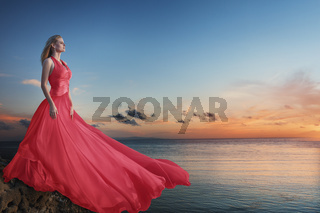 Beautiful young woman posing in red luxurious long dress on the sea beach