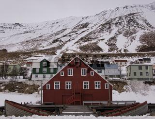 Rotes Holzhaus in Island vor schneebedeckten Berg