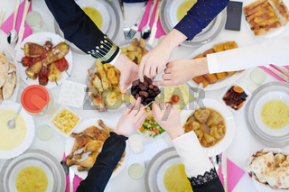 Muslim family having Iftar dinner eating dates to break feast top view