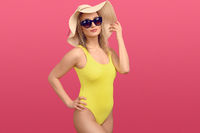 Trendy young woman in a yellow swimsuit
