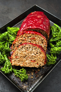 Traditional American meatloaf from ground beef with ketchup and broccoli as closeup on a rustic metal tray