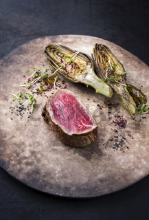 Fried dry aged beef fillet medallion steak natural with artichokes and herbs as closeup on a rustic modern design plate with copy space