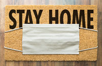 Welcome Mat With Medical Face Mask and Stay Home Text Amidst The Coronavirus Pandemic