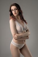 Young brunette in white lace lingerie view
