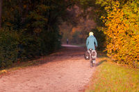 Unrecognizable woman with helmet and outdoor sports clothing riding bicycle with bags on gravel road between beautifully multicolored autumn tree foliage in October