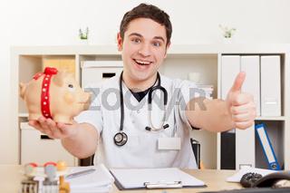 Arzt mit Sparschwein hält Daumen hoch