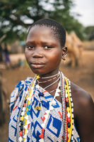 TOPOSA TRIBE, SOUTH SUDAN - MARCH 12, 2020: Teen girl in ornamental garment and with colorful accessories looking at camera on blurred background of Toposa Tribe village in South Sudan, Africa